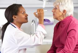 woman doctor giving elderly patient eye exam